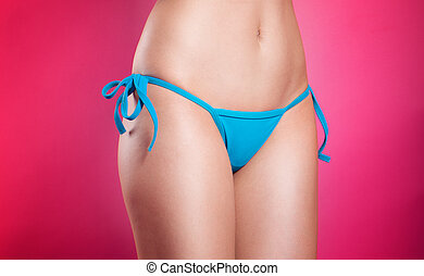 Torso of a young, slim model wearing bikini
