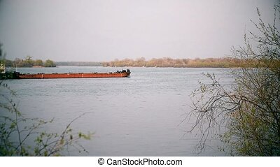 Long cargo barge on a river - Long cargo barge sailing down...