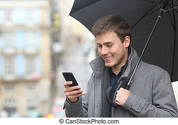 Man using a smart phone in a rainy day