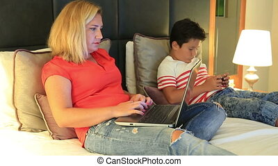 Mother and son using smartphone and laptop in the bedroom