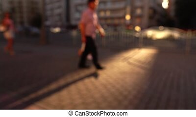 Blurred street in the evening. Cars and pedestrians. 4K...