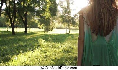 Girl walking in park - Girl walking towards sunset in park