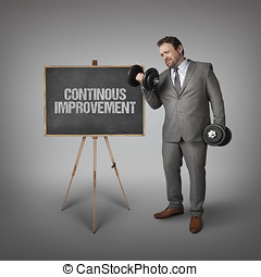 Continous improvement text on blackboard with businessman...