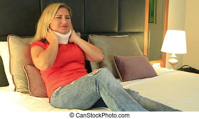 Painful woman with a neck brace lying on a bed and resting