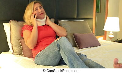Painful woman with a neck brace talking on the phone -...