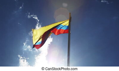 National flag of Colombia on a flagpole in front of blue sky