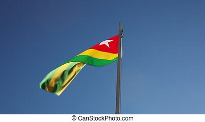 National flag of Togo on a flagpole in front of blue sky
