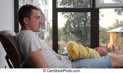 Newborn baby crying lying on a man's lap - Newborn baby...