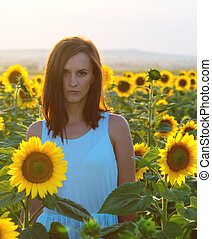 Woman in sunflower field at sunset