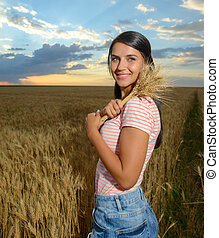 Portrait of beautiful young woman with flowers in the wheat field
