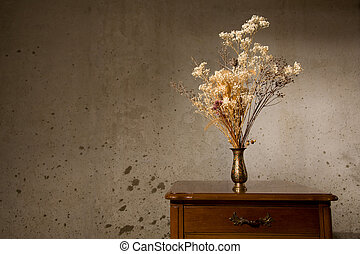 Still life - Vase with dried flowers on a table against...