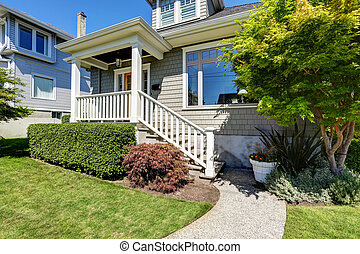 Craftsman house porch with square columns and staircase...