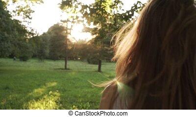 Girl walking in park and shaking hair - Girl walking towards...