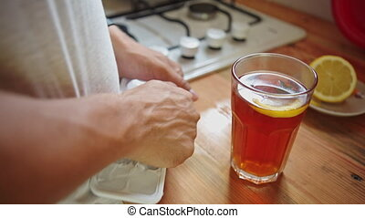 Man in the kitchen preparing tea with ice - Man in the...