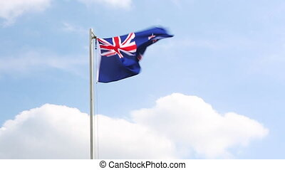 National flag of New Zealand on a flagpole in front of blue...