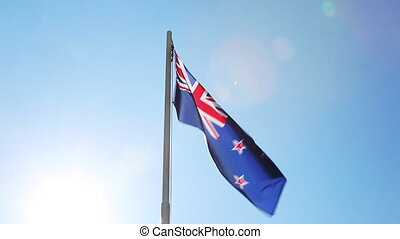 Flag of New Zealand on a flagpole in front of blue sky
