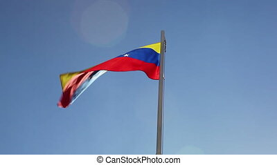 Flag of Venezuela on a flagpole in front of blue sky