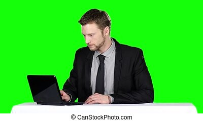 Businessman sitting at the table and uses notebook. Green...