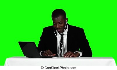 Businessman sitting at a desk and listening to music on headphones. Green screen