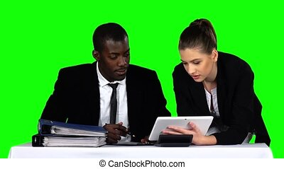 Business people working together while looking at charts in laptop in an office. Green screen
