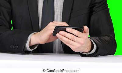 Businessman sitting at the table and uses phone. Closeup....
