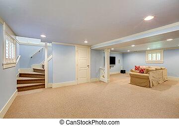 Spacious basement room interior in pastel blue tones