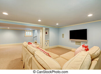 Spacious basement living room interior in pastel blue tones