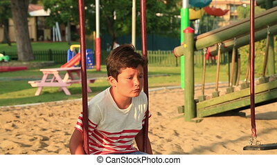 Sad little boy at the playground - Lonely, sad schoolboy...