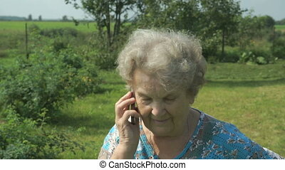 Elderly woman 80s communicates cell phone outdoors - Old...