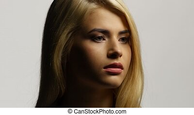 Side view of a beautiful blond woman with her long hair....