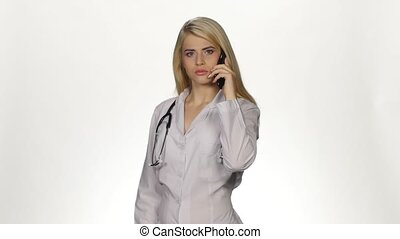 Doctor talking on the phone worried angry. White - Doctor...