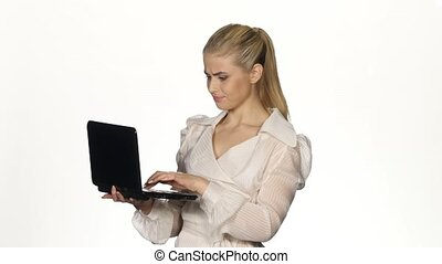 Young angry businesswoman works on notebook. White - Young...