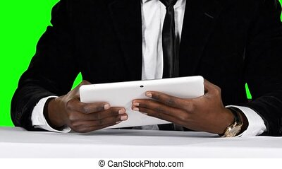 Businessman sitting at the table and uses laptop. Green...