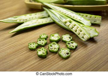 Okra - Sliced okra Vegetables on wooden background