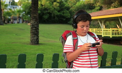 Schoolboy listening to music - Young boy playing with mobile...
