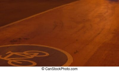 Several bicycles passing by on urban bike path at night. 4K...