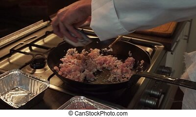 Cooking forcemeat on a frying pan - Male hands cooking...