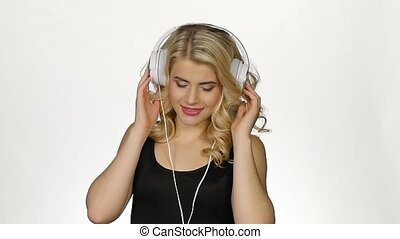 Beautiful curly blonde wearing headphones listening to music. White. Slow motion