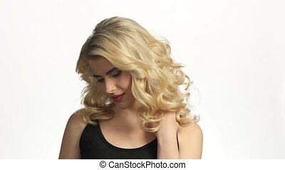 Beautiful pensive woman with long blond curled hair. White