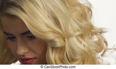 Beautiful young woman with long blond curled hair. White....