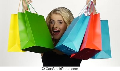 Beautiful blonde holds a lot of different color packages in hands and smiling