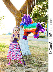 Young girl at an outdoor party hitting a pinata Celebrating...
