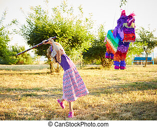 Young girl at an outdoor party hitting a pinata. Celebrating...