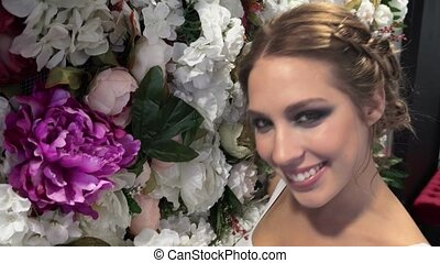 Beautiful girl on the background of flowers and smiling