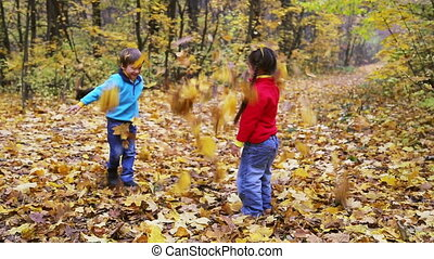 boy and girl throwing up autumn leaves in the forest -...