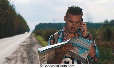 Boy with backpack looking in map at road. Talking on phone. Summer sunny day