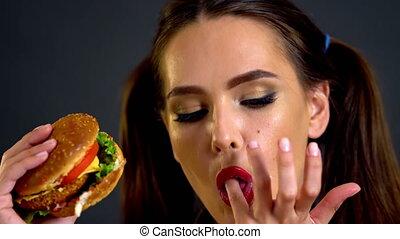 Girl eating hamburger. Girl licking her fingers. Tasty...