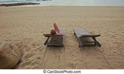 Sand Beach with Woman on Folding Chair Looks at Sea