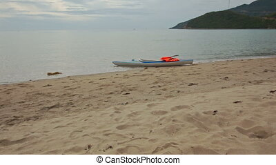 Motion to Canoe on Sand with Life-vests at Azure Sea Edge -...