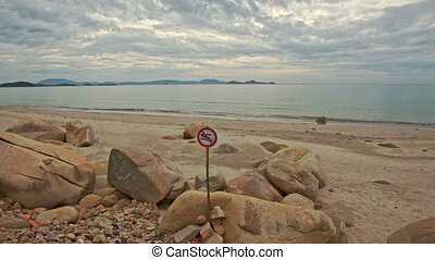 Closeup Sign No Swimming on Rocky Sand Beach